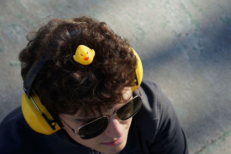 High Angle View Of Yellow Rubber Duck On Young Man Head