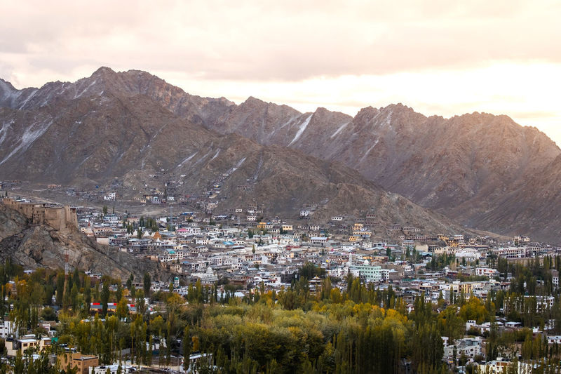 Aerial view of townscape and mountains against sky