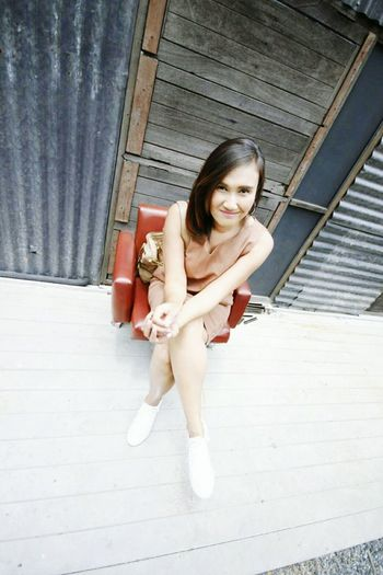 High angle portrait of young woman sitting on chair at porch