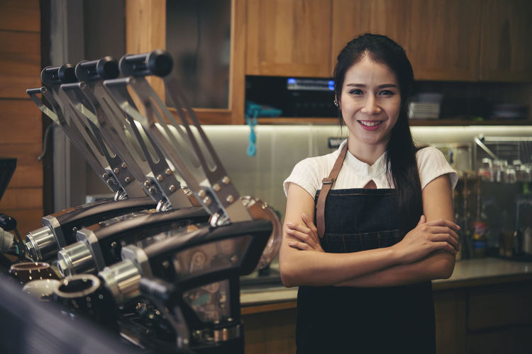 Portrait of a smiling young woman standing in restaurant