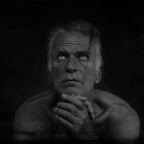 Worried Mature Man Looking Up Against Black Background