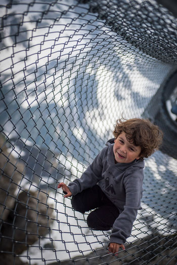 High angle portrait of boy smiling while sitting on net