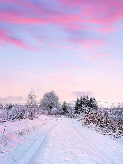 Road On Snow Covered Field Against Sky During Sunset