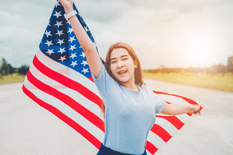 Portrait Of Smiling Teenage Girl With American Flag Standing On Road