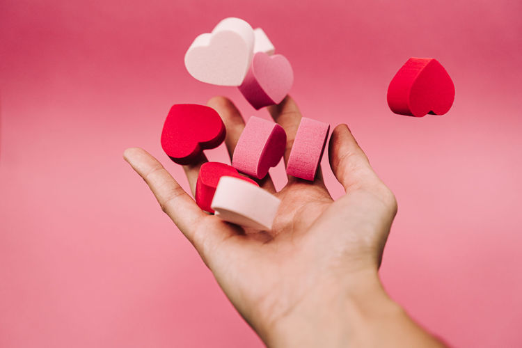 Close-up of hand holding heart shape against pink background