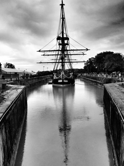 Sailing Ship Moored On River Amidst Retaining Wall Against Cloudy Sky