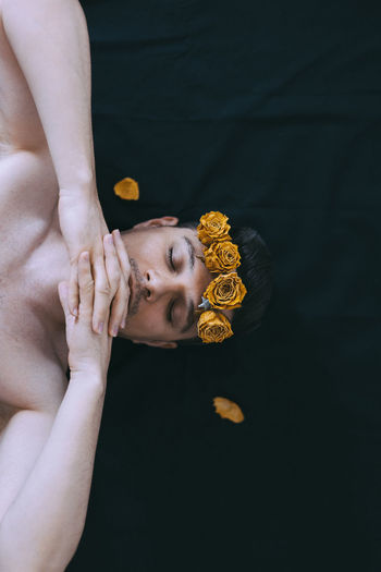 Directly Above Shot Of Shirtless Man Wearing Flowers While Lying Down