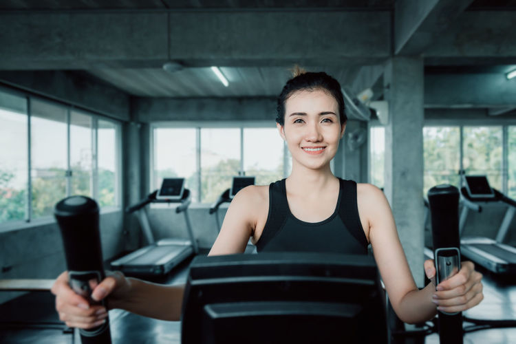 Portrait of smiling young woman on treadmill at gym