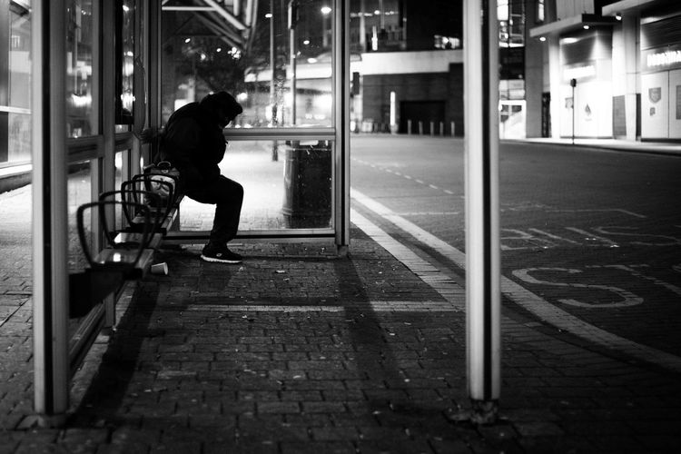 Side view of man sitting on bus sop in city at night