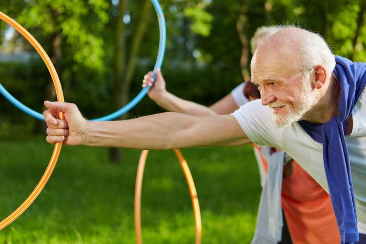 Senior Man Holding Plastic Hoop While Exercising At Park