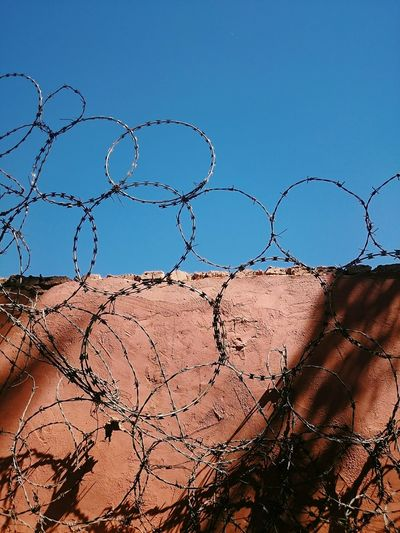 Low angle view of razor wires on surrounding wall against clear blue sky