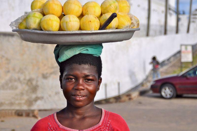 Portrait of teenage girl holding fruits