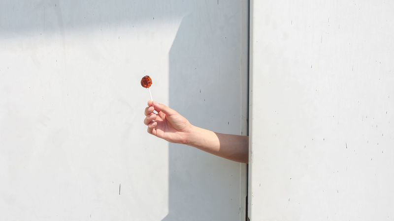 Cheer you up from nowhere. A hand offers a candy through doors. Abstract Backgrounds Candy Day Delivery Doors Fingers Gap Give Hide Holding Human Body Part Human Hand Minimalist Architecture Offering Open Peeking Sweet The City Light Wall White Fresh on Market 2017 The City Light Breathing Space