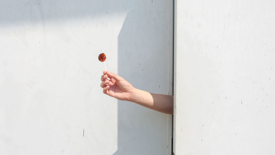 Cheer you up from nowhere. A hand offers a candy through doors. Abstract Backgrounds Candy Day Delivery Doors Fingers Gap Give Hide Holding Human Body Part Human Hand Minimalist Architecture Offering Open Peeking Sweet The City Light Wall White Fresh on Market 2017 The City Light Breathing Space Creative Space The Creative - 2018 EyeEm Awards