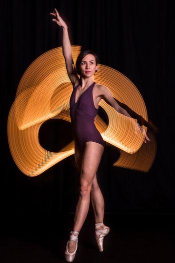 Full length of dancer against light painting