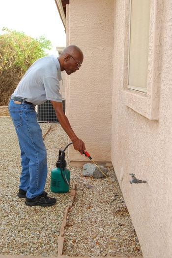 Side view of mature man spraying crop sprayer in back yard