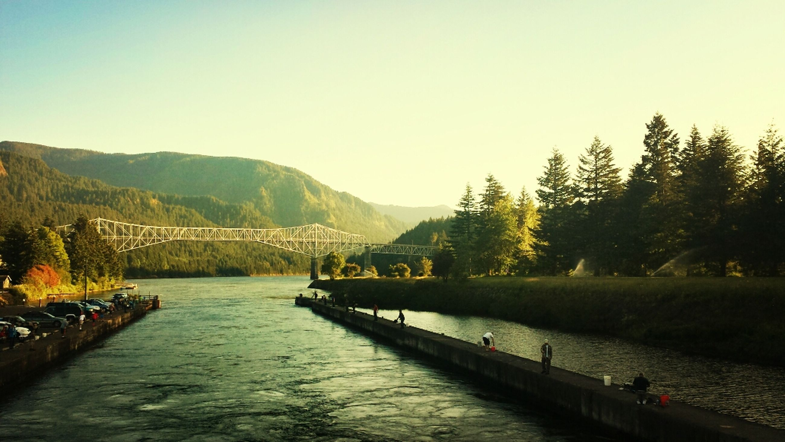 water, mountain, tranquil scene, clear sky, tranquility, scenics, beauty in nature, tree, lake, nature, copy space, mountain range, river, transportation, waterfront, nautical vessel, idyllic, non-urban scene, sky, incidental people