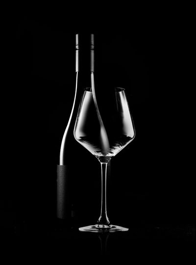 Close-up of wine glass on table against black background