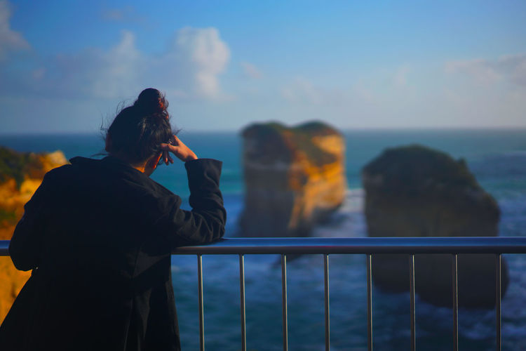 Rear view of woman photographing by sea against sky