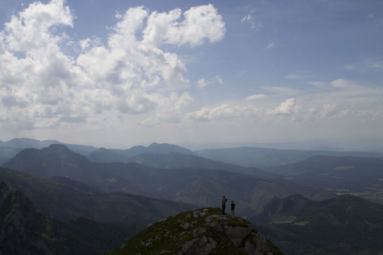 High Angle View Of People Standing On Mountain Against Sky