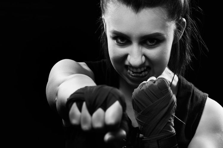 Portrait of young woman against boxing black background