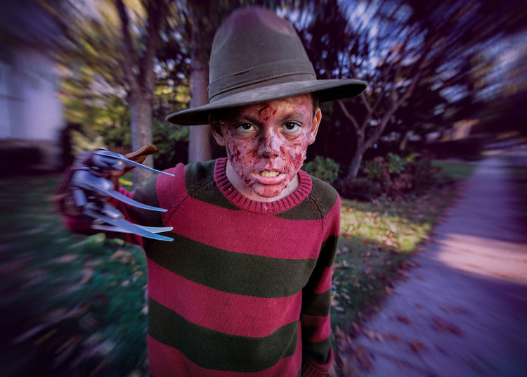 Portrait of serious boy dressed as murderer on street during halloween