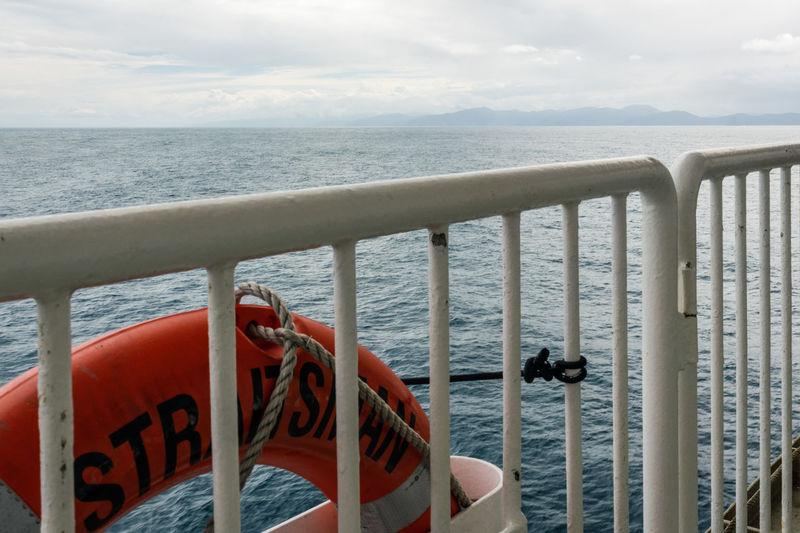 Railing by sea against sky