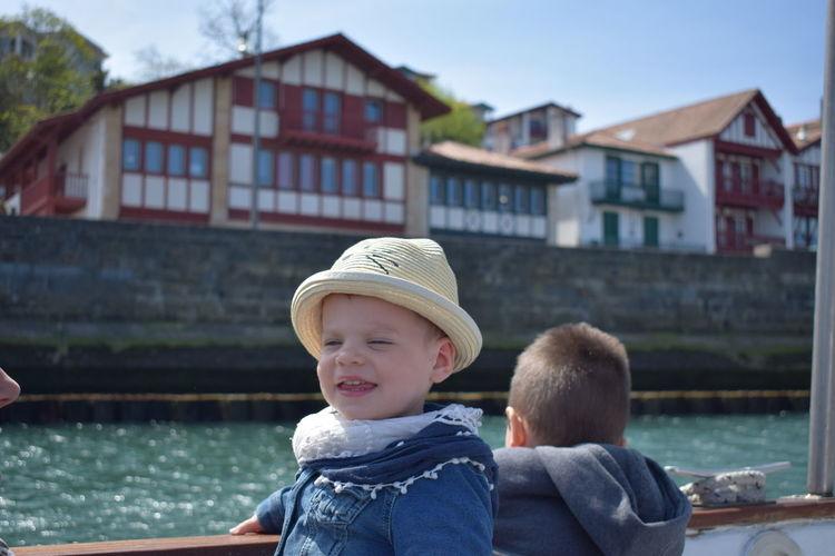 Siblings in boat on river against buildings