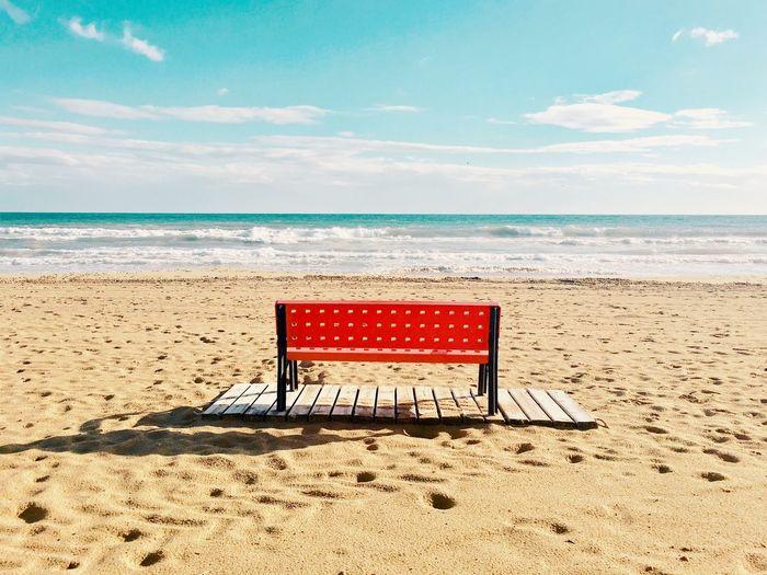 Chair on beach against sky