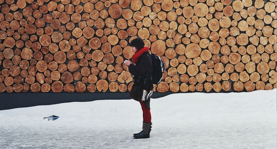 Cold Temperature Day Full Length Log Nature One Person Outdoors People Snow Stack Standing Warm Clothing Winter Wood - Material Woodpile Young Adult