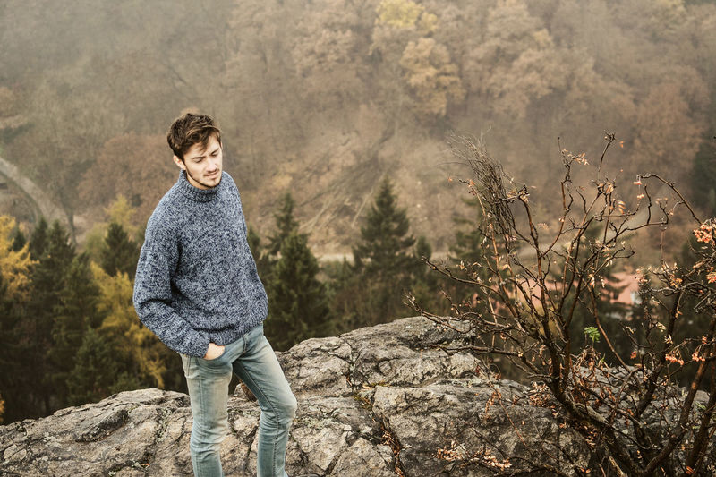 Portrait of a young man standing on mountain in autumn
