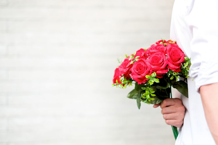 Midsection Of Man Holding Rose Bouquet Against Wall