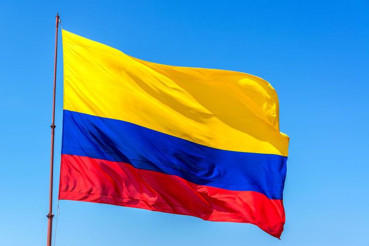 Low angle view of colombian flag against clear blue sky