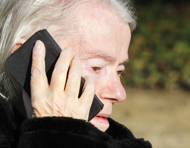 Close-Up Of Senior Woman Answering Mobile Phone Outdoors