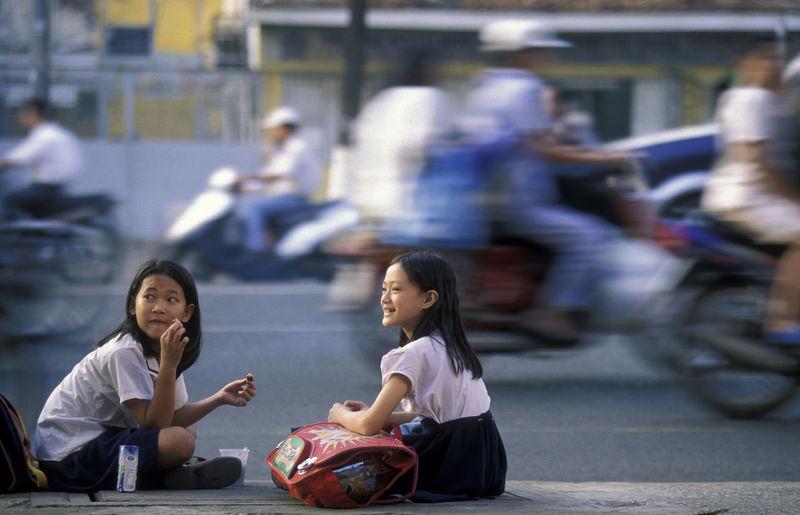 Blurred Motion Of People By Schoolgirls Sitting On Street