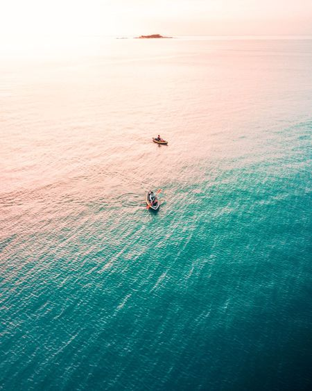 High angle view of people in canoes on sea during sunset