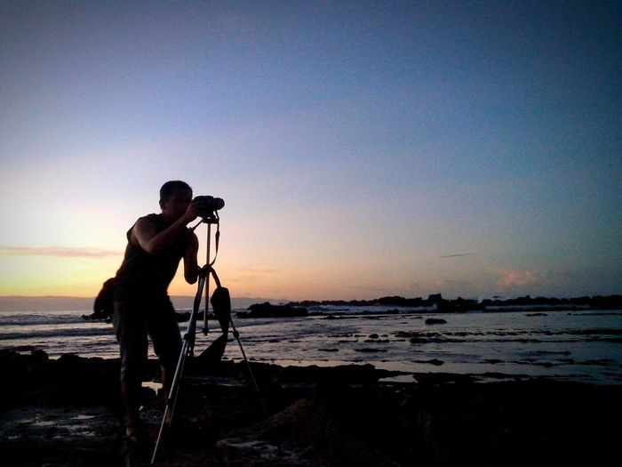 Man with tripod on shore against sky at beach during sunset
