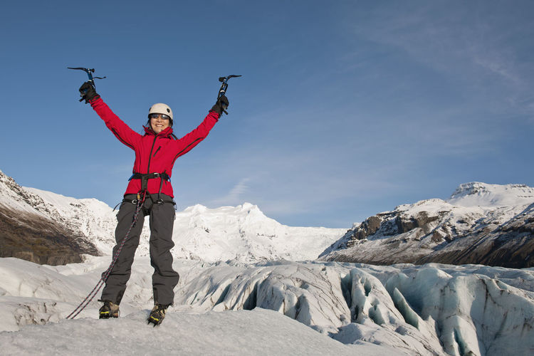 Full length of person standing on snow covered mountain against sky