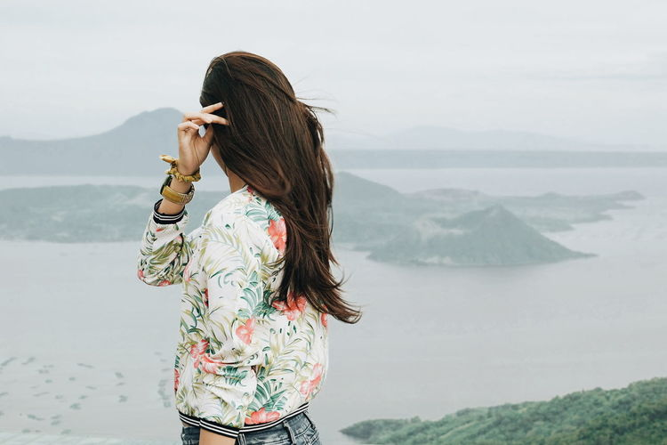Side view of girl looking at view of taal volcano island
