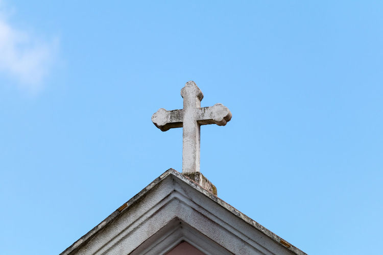 High section of church with cross against sky