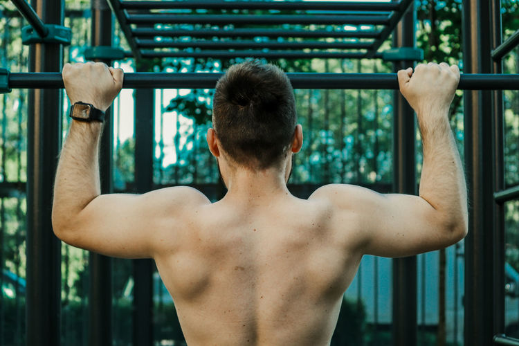 Rear view of shirtless man looking at camera