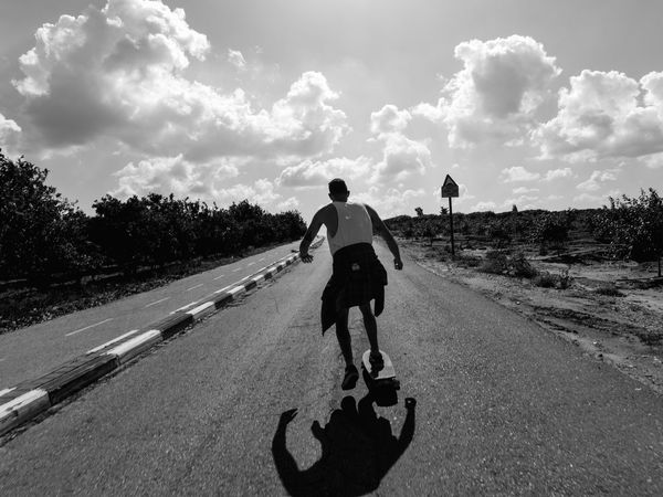 Skateboarding Downhill Transportation Full Length Low Angle View Shadow Blackandwhite People And Places Bicycle Tree Riding Cloud Road Sky Men Rear View On The Move Countryside Leisure Activity Lifestyles Road Marking Motion Mode Of Transport Sunlight Sport