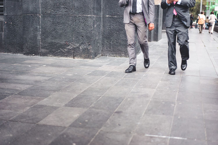 Low Section Of Businessmen Walking On Footpath