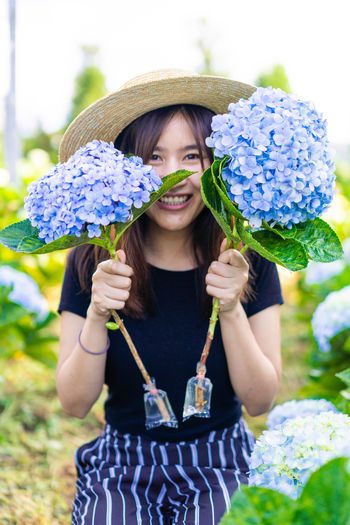 Smile and Hydrangea Portrait Hydrangea Hydrangea Flower Hydrangea In Bloom Hydrangea Bush Flower Asian  Garden Hat Cute Women Front View Flowering Plant One Person Holding Leisure Activity Plant Fragility Real People Smiling Happiness Freshness Emotion Vulnerability  Nature Lifestyles Looking At Camera Day Outdoors Flower Head Hairstyle Purple