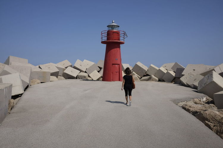 Architecture Beach Building Exterior Clear Sky Day Direction Full Length Guidance Lighthouse Men One Person Outdoors People Protection Real People Safety Sky Standing