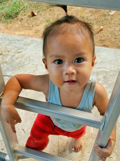 Portrait of cute baby boy standing by ladder