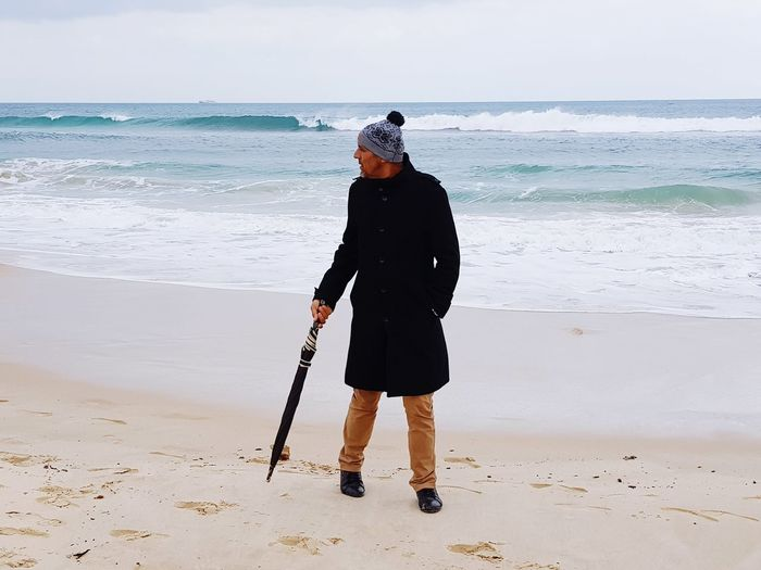 Full length of man holding umbrella while walking at beach