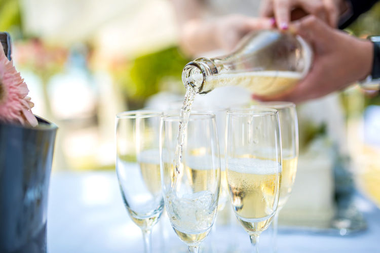 Cropped Hand Pouring Champagne In Flute