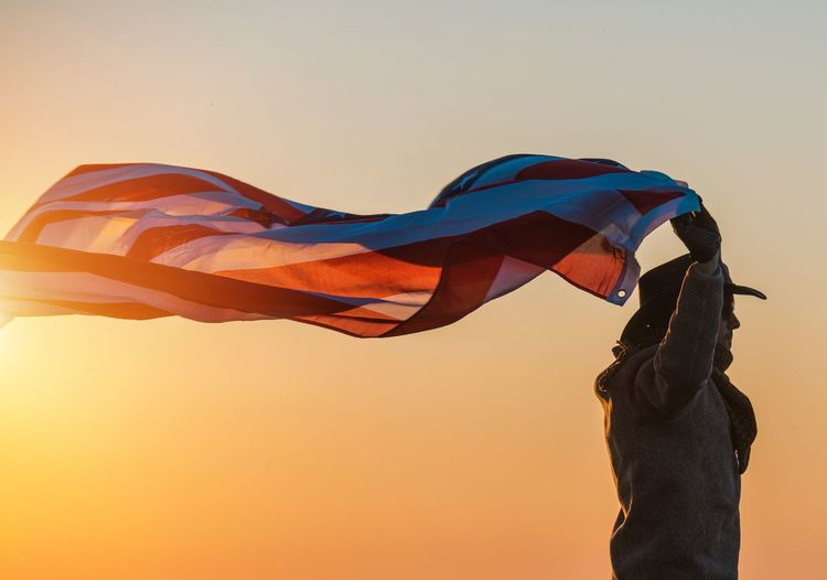 Low angle view of man waving flag against clear sky during sunset