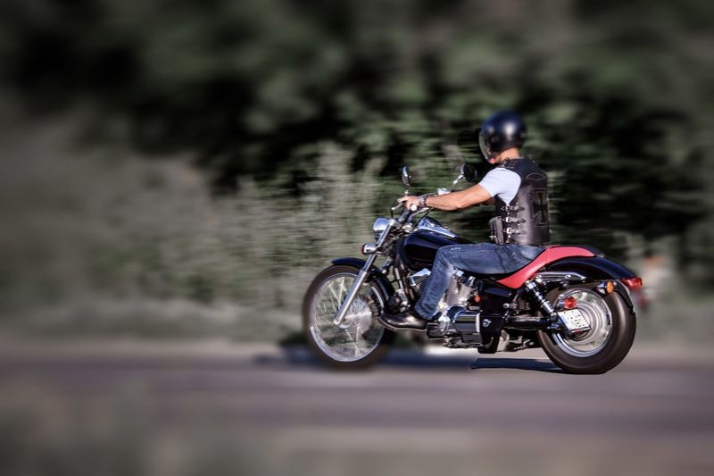 Side view of man riding motorcycle